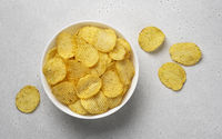 Ridged potato chips in bowl, top view