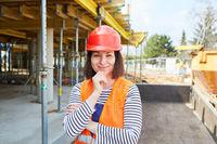 Frau mit rotem Schutzhelm auf einer Baustelle