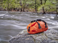 small waterproof duffel on a river shore
