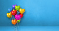 Colorful heart shape balloons bunch on a blue wall background. Horizontal banner.