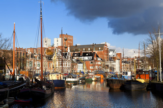 sunny canal in Groningen with many river boats