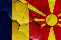flags of Romania and North Macedonia painted on cracked wall