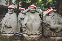 Detail of Buddha statues with knitted hat offerings at the temple Diasho-in in Miyajima, Japan