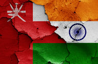 flags of Oman and India painted on cracked wall