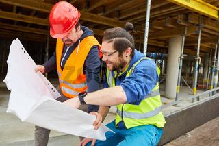 Handwerker und Bauarbeiter mit Bauzeichnung