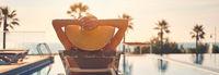 Rear view woman wear hat sunbathing on deckchair on poolside