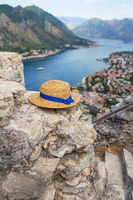 A straw hat lies on the ruins - an incredibly beautiful view of the Bay of Kotor on a beautiful summer day in Montenegro. Very beautiful view of the fjord from above.