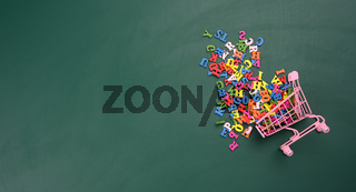 scattered multicolored letters of the english alphabet from a miniature shopping cart on a green background
