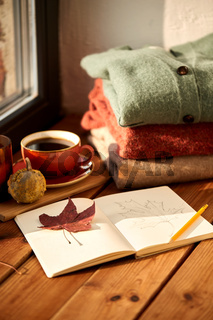 sketchbook, autumn leaf and coffee on window sill