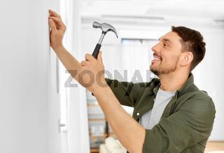 smiling man hammering nail to wall at home