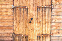 Old wooden gate with massive metal hinges
