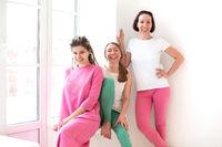 Three happy ladies having break during yoga training in gym, sitting on windowsill on sunny morning