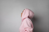 Side portrait of woman pulling the hood over the heads. Isolated on white wall.