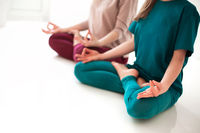 Two female in sportswear sitting with crossed legs and mudra hands on mat and doing yoga while practicing mindfulness
