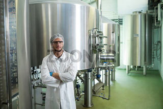 Portrait of scientist with arms crossed standing at factory