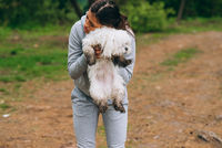 Beautiful woman holding a dog in her arms
