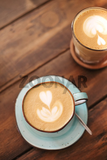 Mugs with latte on wooden table
