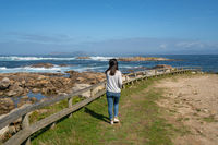 Woman walking on the coast of Galiza in the north of Spain with atlantic ocean and Cies Islands on the background