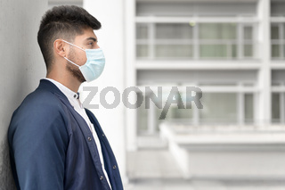 Handsome young man standing outdoors in medical mask. Coronavirus concept.