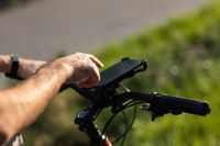 Man planning route using GPS navigation application in mobile phone on his bicycle bike.