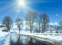 Spring sunshine and road through the alpine village in Austria with reflection of trees in thawing snow.