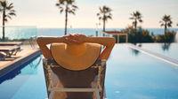 Rear view woman wear hat lying on deckchair on poolside