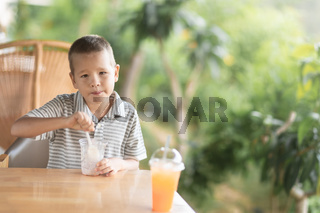Boy eating ice-cream in outdoor cafe