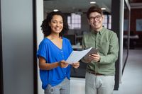 Portrait of smiling diverse male and female colleague with paperwork and tablet standing in office