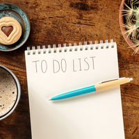 To do list, square overhead shot of a notebook on a wooden desk, with a blue pen