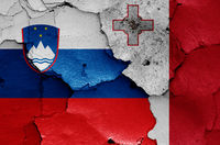 flags of Slovenia and Malta painted on cracked wall