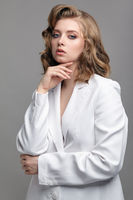Portrait of young dark blonde woman in casual white jacket with hands near face.
