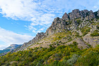 Autumn mountain landscape-rocky stone mountains covered with green bushes against a blue sky with white clouds on a sunny day
