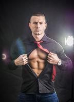 Muscleman opening his shirt revealing muscular torso