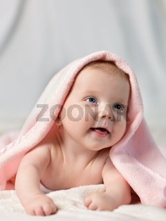 Charming baby. Beautiful baby under pink towel