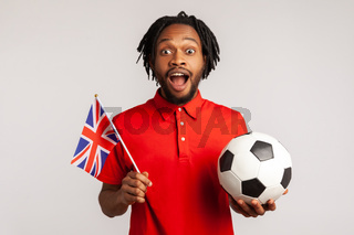 Excited amazed man with dreadlocks wearing red casual style T-shirt, holding british flag and soccer black and white ball, united football league.