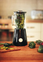 Green vegetable smoothie blender machine in kitchen with kale leaves inside
