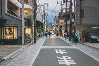 Normal post-covid Japanese street life at small road with power lines in the evening, Kyoto, Japan