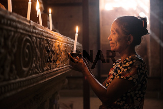 Asian woman praying with candle light