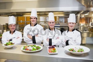 Smiling Chef's standing behind salads
