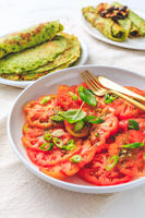 Tomato salad with onions and ramson pancakes or crepes on white background