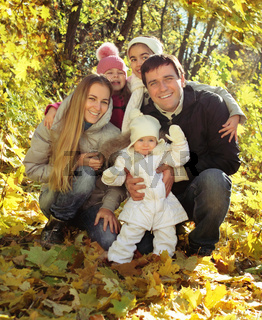 Young happy family in autumn forest
