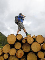 photographer standing on a stack of wooden logs