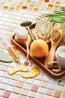 Jars of cream for face and body care, gold eye patches and serum with gold, jade roller massager gau-sha and massager and body brush against background of tile mosaic