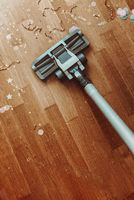 Vacuum cleaner nozzle on wooden floor parquet with confetti, cleaning after Christmas holidays.