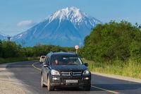 Black Mercedes-Benz car driving on asphalt road on background summer landscape, volcano