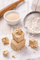 Fresh and dried yeast with baking ingredients on white background