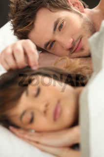 Young man watching his partner sleep in bed