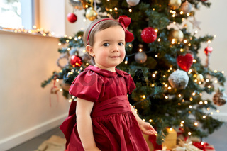 lovely baby girl over christmas tree at home