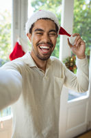 Portrait of happy biracial man in santa hat making christmas video call
