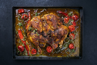 Traditional barbecue spatchcocked chicken al mattone chili with tomatoes and jalapeno served as top view on an old rustic metal tray